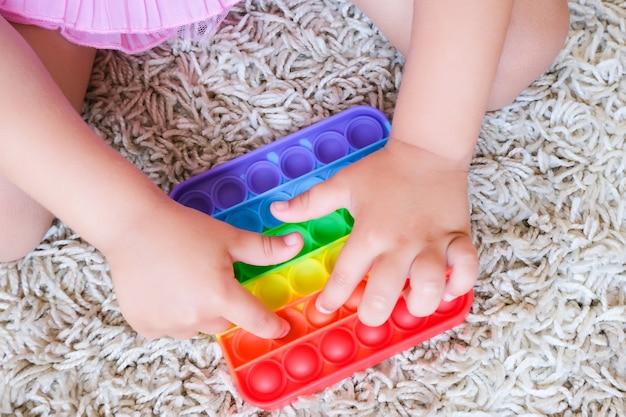 Dzieci bawią się zabawką sensoryczną pop it. ulga w stresie i niepokoju. modna gra w kręcenie silikonem dla zestresowanych dzieci i dorosłych. miękkie zabawki z bąbelkami.