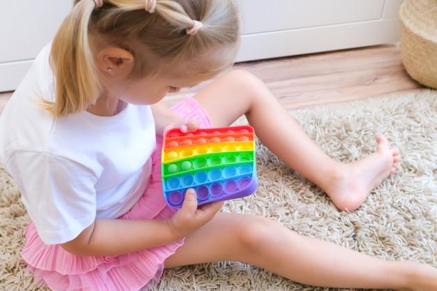 Dzieci bawią się zabawką sensoryczną pop it. ulga w stresie i niepokoju. modna gra w kręcenie silikonem dla zestresowanych dzieci