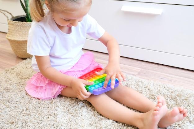 Dzieci bawią się zabawką sensoryczną pop it. ulga w stresie i niepokoju. modna silikonowa gra w wiercenie dla zestresowanych dzieci
