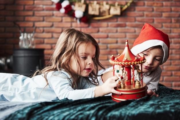 Dzieci bawią się zabawkową karuzelą w nowym roku. jedna dziewczyna ma na głowie czapkę mikołaja.
