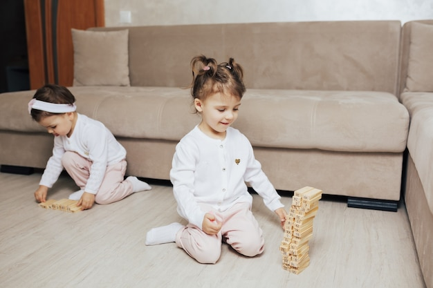 Dzieci bawiące się drewnianymi klockami w domu w salonie