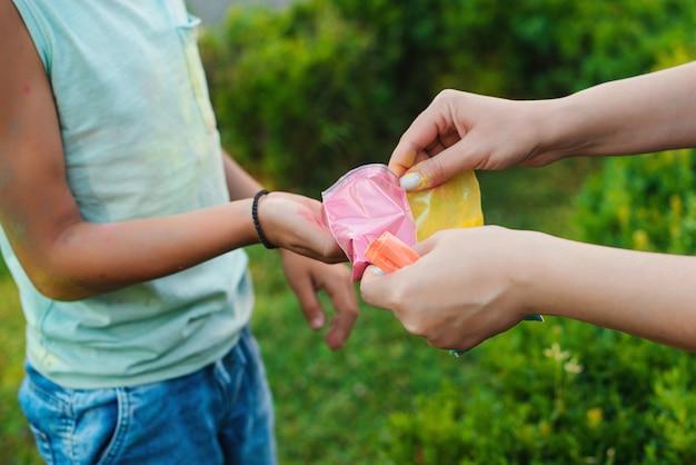 Dzieci bawiące się kolorowym proszkiem. święto holi. przyjaciele bawią się podczas święta holi. szczęśliwe dzieciństwo. pre teen chłopcy bawiący się kolorami. koncepcja indyjskiego festiwalu holi.