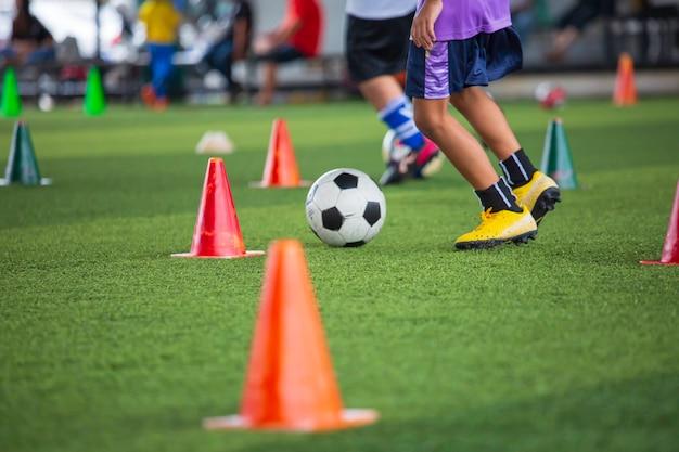 Dzieci bawiące się kontrolną taktykę piłki nożnej na boisku z tłem treningowym trening dzieci w piłce nożnej
