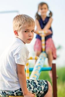 Dzieci bawiące się na huśtawce. chłopiec w centrum uwagi i dziewczynka niewyraźne za.