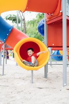 Dzieci bawiące się na placu zabaw w letnim parku na świeżym powietrzu