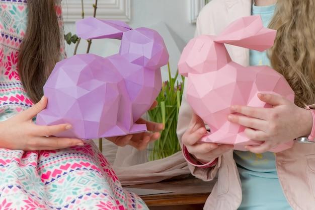 Dzieci bawiące się na wielkanoc z królikami z papieru