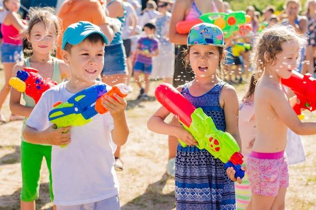 Dzieci bawiące się na zewnątrz z armatek wodnych w piękny słoneczny dzień
