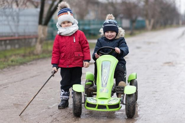 Dzieci bawiące się na zewnątrz z wózkiem