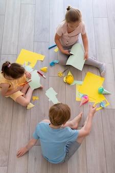 Dzieci bawiące się papierowym pełnym ujęciem