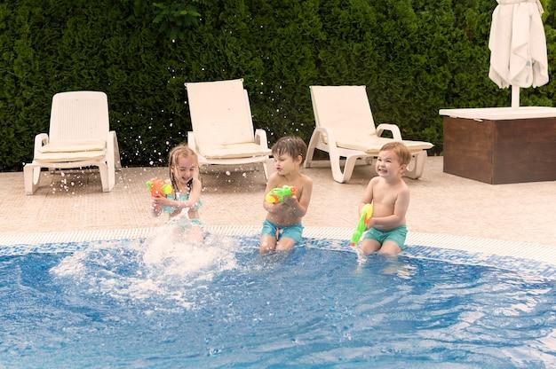 Dzieci bawiące się pistoletami na wodę