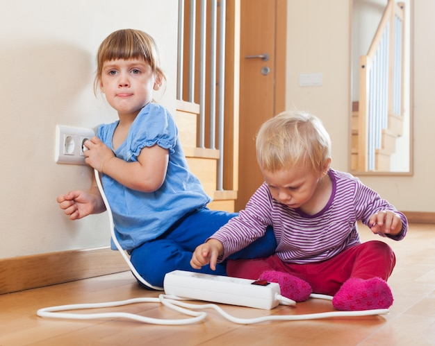 Dzieci bawiące się przedłużeniem i wylotem elektrycznym