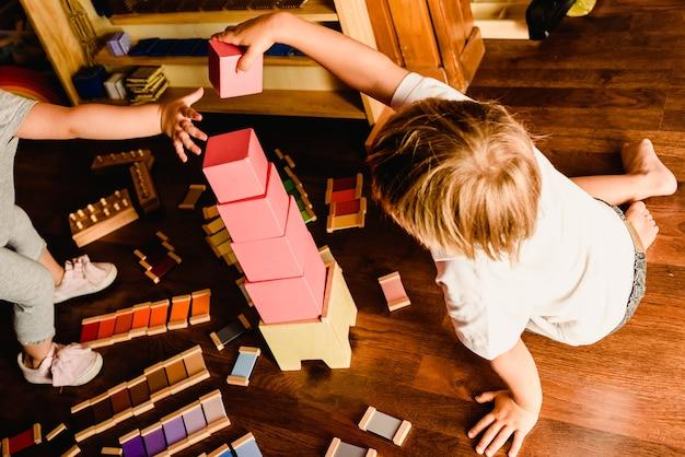 Dzieci bawiące się różową wieżą w klasie montessori