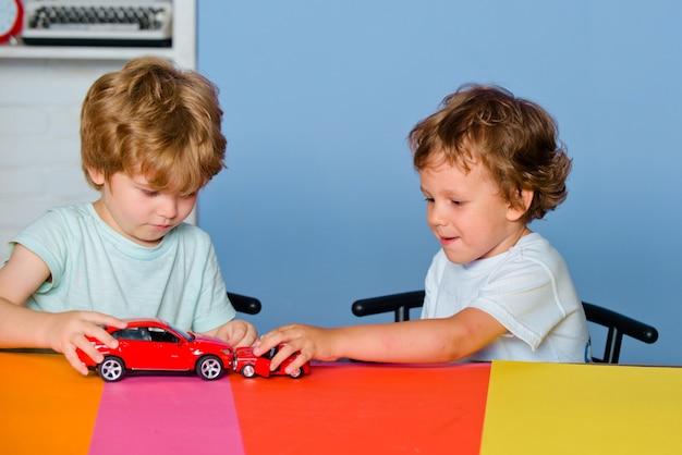 Dzieci bawiące się samochodzikiem w przedszkolu. dziecko ze szkoły podstawowej. kaukascy chłopcy bawią się kolorowymi samochodzikami.
