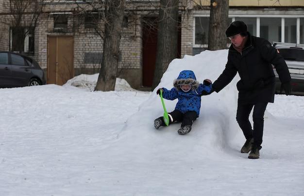 Dzieci bawiące się śniegiem zimą na podwórku w mieście