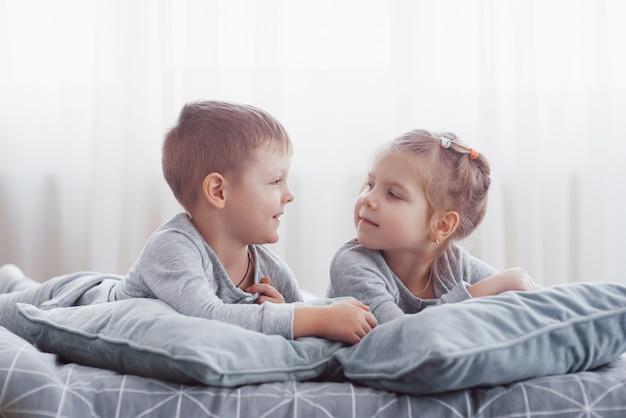 Dzieci bawiące się w łóżku rodziców. dzieci budzą się w słonecznej białej sypialni. chłopiec i dziewczynka bawią się w pasujących piżamach. bielizna nocna i pościel dla dzieci i niemowląt. wnętrze pokoju dziecinnego dla malucha. poranek rodzinny