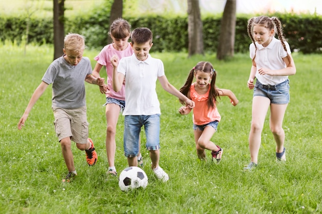 Dzieci bawiące się w piłkę nożną na zewnątrz