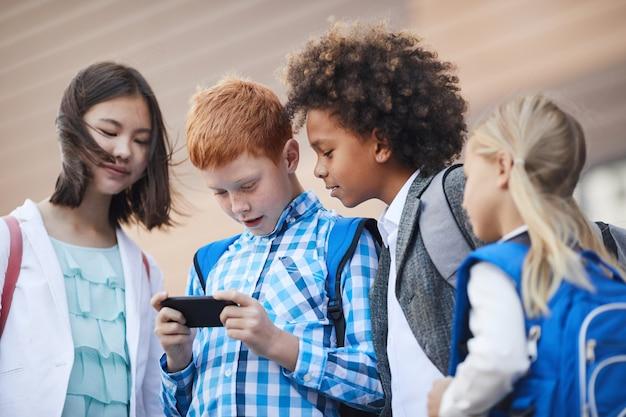 Dzieci bawiące się w telefonie komórkowym