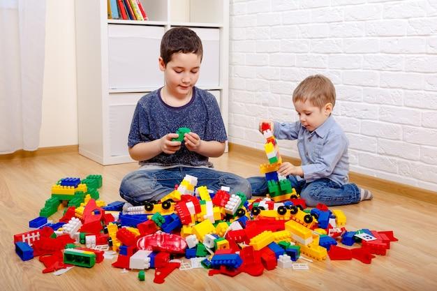 Dzieci bawiące się z konstruktorem w domu. dzieci w wieku przedszkolnym świetnie się bawią. opieka dzienna, rozwój dzieci