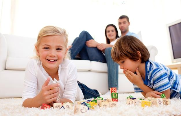 Dzieci bawiące się z kostki alfabetu w domu