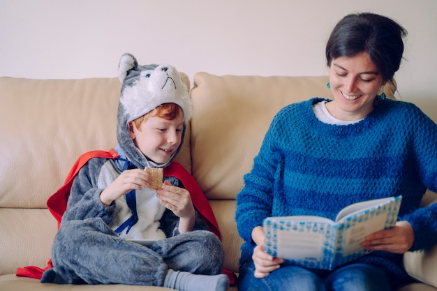 Dzieci bez szkoły spędzają czas w domu w domu. rodzinny styl życia w pomieszczeniu. młoda matka czyta interesującą książkę dla swoich dzieci ubranych w kostiumy karnawałowe. opowiadacz czasu z mamą.
