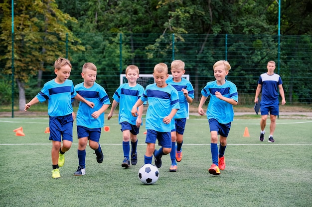 Dzieci biegają i kopią piłkę nożną na treningu piłkarskim dzieci
