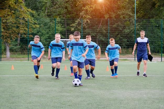 Dzieci biegają i kopią piłkę nożną na treningu piłki nożnej