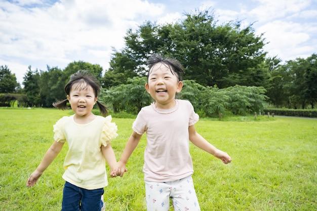 Dzieci biegają po łące w parku