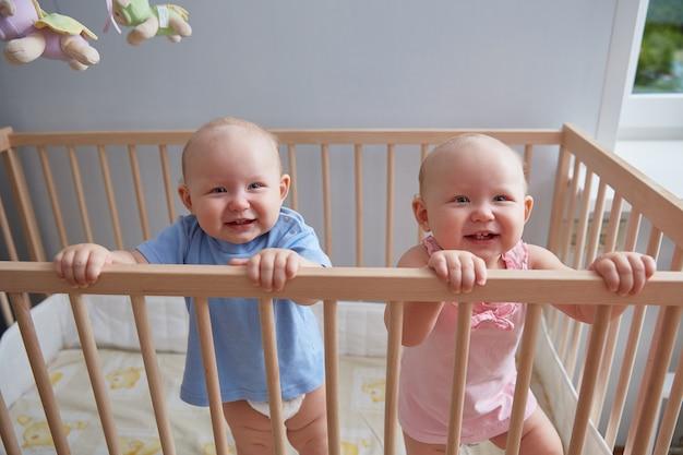 Dzieci bliźniaki chłopiec i dziewczynka uśmiechają się, stojąc w łóżeczku
