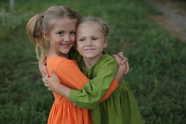 Dzieci blondynki w żółto-zielonej sukience przytulają się na tle przyjacielskiego ogrodu