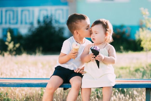 Dzieci, brat i siostra na ławce jedzą lody brat całuje swoją siostrę w policzek bardzo uroczo