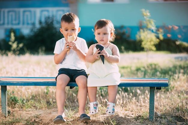 Dzieci, brat i siostra na ławce jedzą lody są bardzo zabawne i urocze