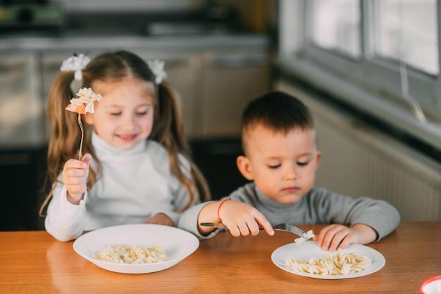 Dzieci chłopca i dziewczynki w kuchni jedzące kiełbaski z makaronem są bardzo zabawne i przyjazne, bardzo słodkie