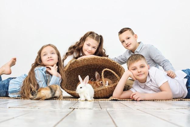 Dzieci chłopcy i dziewczęta szczęśliwe piękne puszyste małe króliki na białym tle ściany