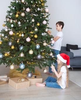 Dzieci - chłopiec i dziewczynka bawią się przy choince. wnętrze salonu z choinką i dekoracjami. nowy rok. rozdawanie prezentów.