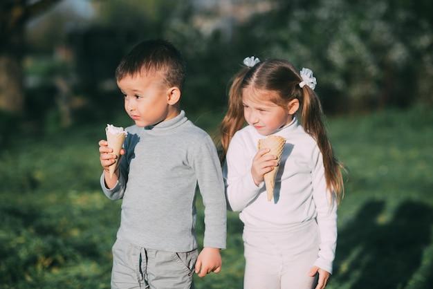 Dzieci chłopiec i dziewczynka jedzą lody na zewnątrz na tle trawy i drzew bardzo słodkie