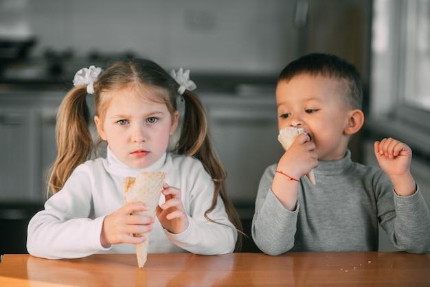 Dzieci chłopiec i dziewczynka jedzą lody w kuchni to świetna zabawa bardzo słodka