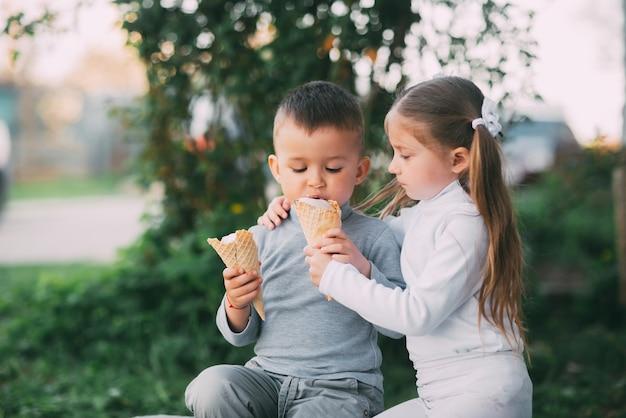 Dzieci chłopiec i dziewczynka jedzenie lodów na zewnątrz na tle trawy i drzew bardzo słodkie