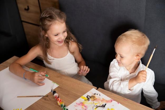 Dzieci chłopiec i dziewczynka razem malują obrazki. kreatywność dla dzieci. rysować