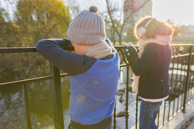 Dzieci chłopiec i dziewczynka stojąc plecami na moście, patrząc na kaczki