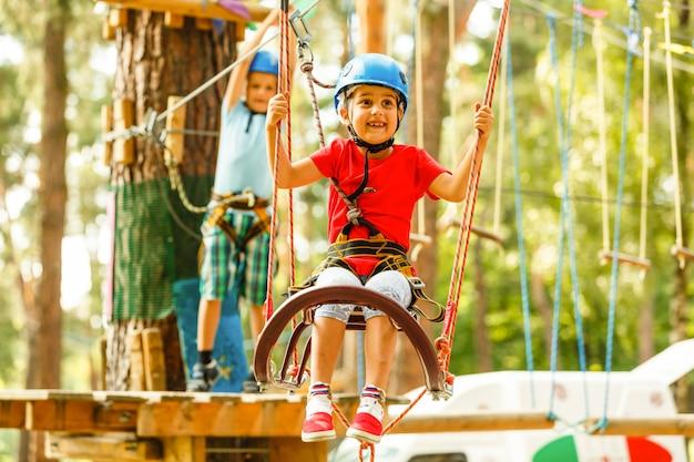 Dzieci, chłopiec i dziewczynka w parku linowym mijają przeszkody. brat i siostra wspinają się na linową drogę