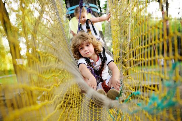 Dzieci - chłopiec i dziewczynka w parku linowym mijają przeszkody.