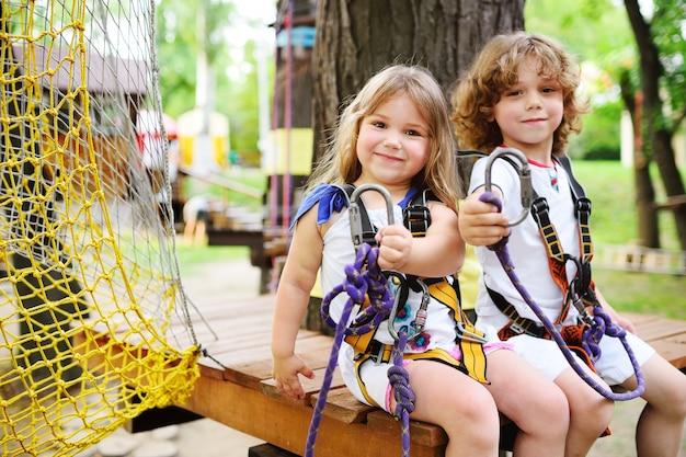 Dzieci - chłopiec i dziewczynka w parku linowym mijają przeszkody