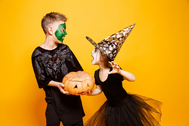 Dzieci chłopiec i dziewczynka w różnych kostiumach na halloween, uśmiechając się i walcząc o dyni na białym tle