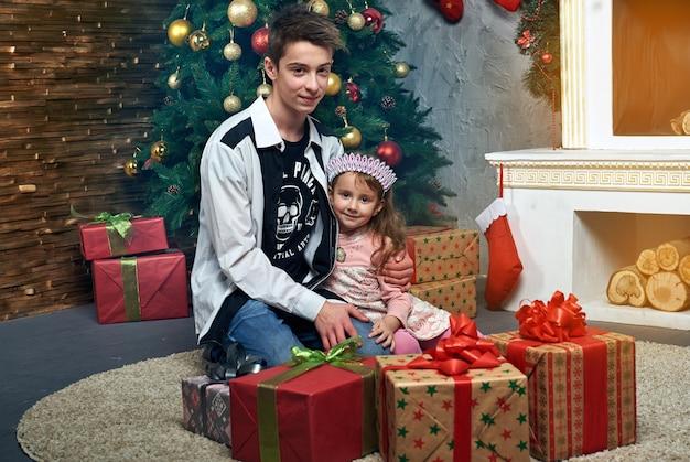 Dzieci, chłopiec i dziewczynka, wiele prezentów, kominek świąteczny i nowy rok
