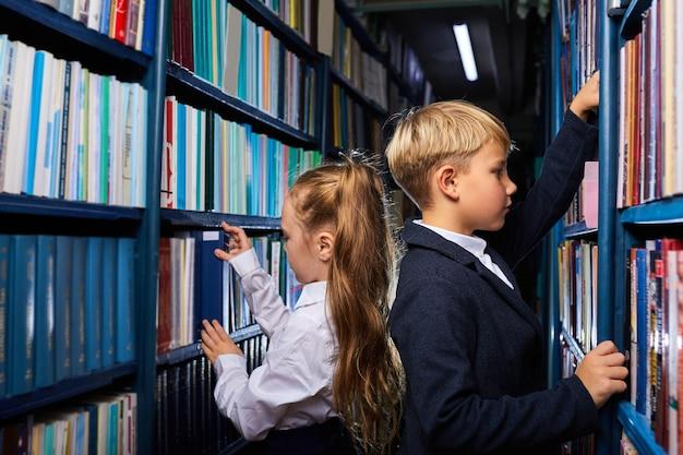 Dzieci chłopiec i dziewczynka wybierają książki w bibliotece do szkoły, idą czytać, zdobywać wiedzę