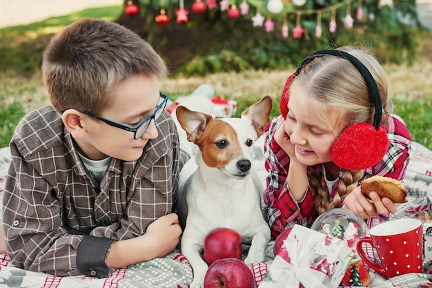 Dzieci chłopiec i dziewczynka z psem jack russell terrier w pobliżu choinki z prezentami,