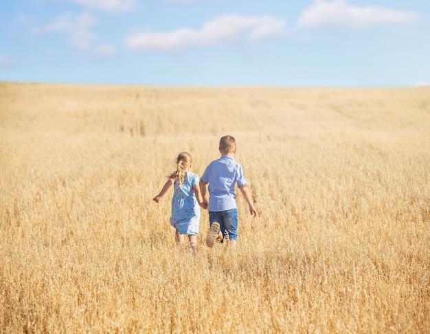 Dzieci chodzą po polu pszenicy z polnymi kwiatami w jasny słoneczny letni dzień