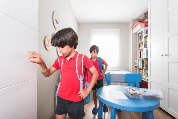 Dzieci chodzą w pokoju z plecakami