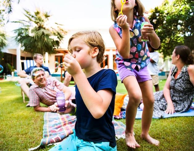 Dzieci cieszą się dmuchaniem bańki na zewnątrz
