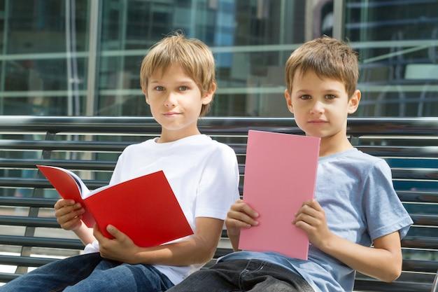 Dzieci czytają książki podczas nauki na świeżym powietrzu
